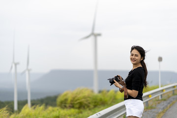 Asian women are very happy to photograph windmills and grasslands.