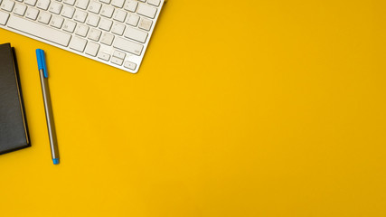 Wall Mural - workspace desk with keyboard and notebook copy space background yellow