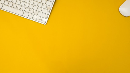 Wall Mural - workspace desk with keyboard and mouse copy space background yellow