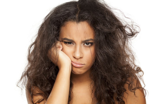 portrait of a unhappy young dark-skinned woman with messy long hair on a white background