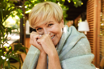 Lovely mature woman wrapped in blanket relaxing