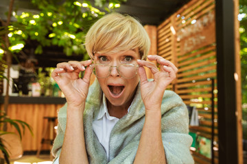 Excited mature woman in eyeglasses