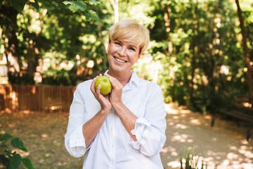 Happy mature woman holding green apple
