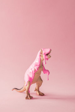 Pink paint dripping on dinosaur toy. Creative minimal concept.