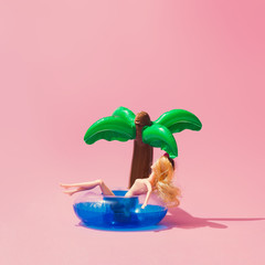 Tropical palm inflatable toy with doll on pink background. Creative minimal beauty summer concept.