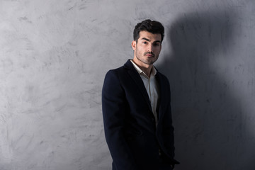 A serious handsome young businessman in a black suit standing in front of a grey wall in a studio.