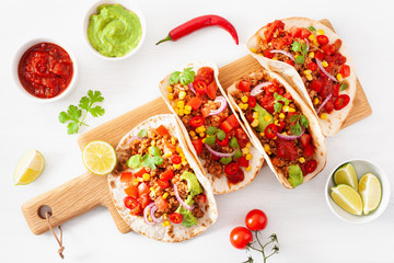 mexican beef and pork tacos with salsa, guacamole and vegetables
