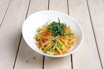 Salad with fresh cucumber, pepper, cabbage, carrot, seaweed and sesame