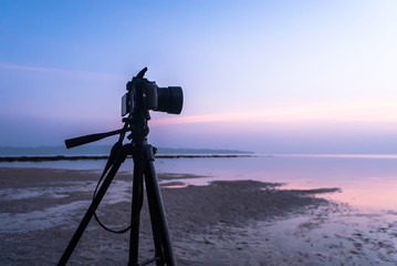 Dslr digital professional camera stand on tripod photographing sea,
