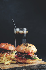 homemade juicy burgers on wooden board. Street food, fast food. with French fries and glass of  cola. toned image