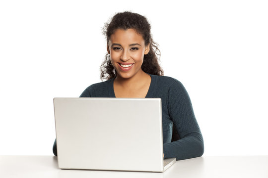 Smiling and positive happy young african-american woman with beautiful face using laptop computer, working project at desk on white background