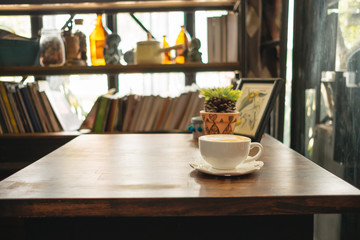 cup of coffee with plants and picture frame place on top of wooden table in living room has bookshelf background