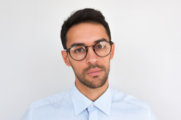 Closeup portrait of handsome serious male, looks directly at the camera, wears round spectacles, isolated over white studio background. Portrait of smart unshaven businessman wears blue shirt. People