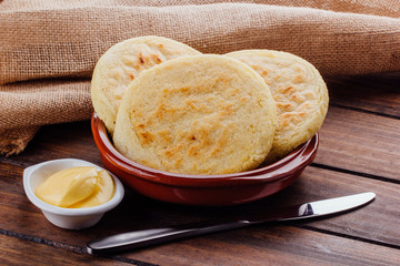 Plate with arepas and butter aside on a rustic wooden background