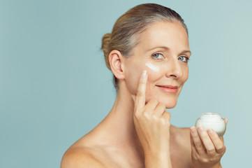 Mature woman applying skin cream on face