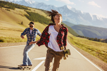 Happy friends with skates and longboards at straight road