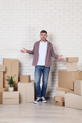 Young man with cardboard boxes on brick wall background