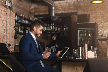 Young man sitting at bar counter and using digital tablet