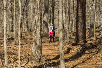 Woman with prosthetic leg hiking on a trail in the woods