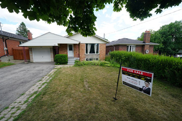 'For Sale' sign is pictured in the front yard of a house in Toronto