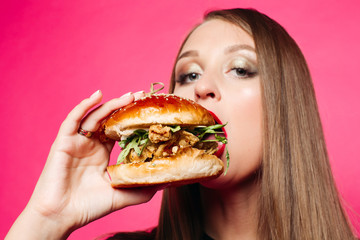 Close-up of pretty long-haired girl biting delicious burger with chicken and salad, looking at camera against pink background. American fast food concept.