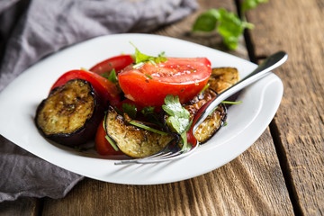 Salad of baked eggplants and fresh tomatoes with parsley