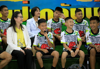 The 12 soccer players and their coach react as the explain their experience in the cave during their news conference in the northern province of Chiang Rai