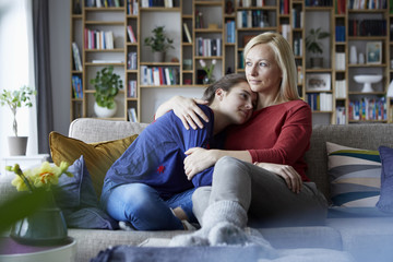 Mother and adolescent daughter sitting on couch with arms around