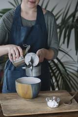 Woman preparing batter for homemade vegan chickpea cookies, partial view