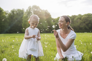 Mother and daughter with blowballs on meadow in summer