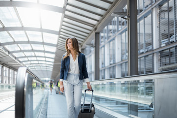 Smiling young businesswoman with baggage on moving walkway