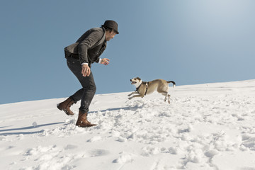 Man playing with dog in winter, throwing snow
