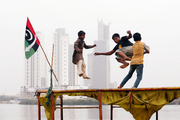Children play on a trampoline, near electoral flag of a political party, with the under-construction buildings in the background, in a low-income neighborhood in Karachi,