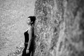beautiful brunette girl resting against rock wall with closed eyes