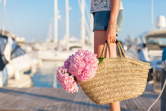 Traveler is standing in yachts port near sea with straw bag and pink flowers hydrangea. Girl has vacation in resort.