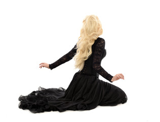 full length portrait of blonde girl wearing corset and long black gown. isolated on white studio background,