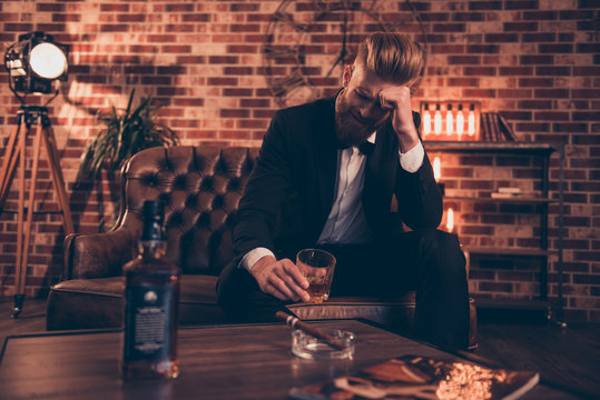 Sad unhappy upset disappointed crying troubled virile freelancer drinking alcohol beverage smoking cigarette holding glass in hand having trouble with business sitting on leather divan at home