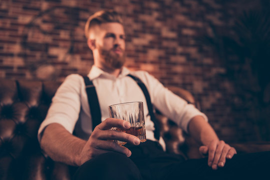 Handsome wealthy confident serious relaxed stunning wealthy successful professional brutal chic elegant posh classy model sitting in chair enjoying whiskey in hand glass is in focus
