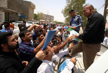Iraqi protesters hand over job requests to government employees in Basra