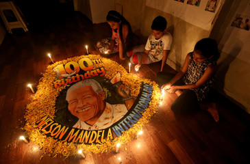 Children light candles beside a painting commemorating South African revolutionary Nelson Mandela's 100th birth anniversary at an art school in Mumbai