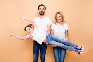 Cheerful smiling bearded father and blonde happy mother carring their little daughter offspring in their arms on beige background