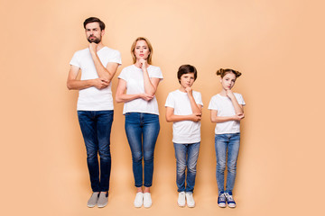 Full length portrait of beautiful  family bieng confused, bearded father, blonde mother and their children wearing jeans and T-shirts, standing straight showing uncertain gesture their hands to chins