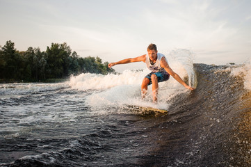 Muscular and strong wakesurfer riding down the river on board