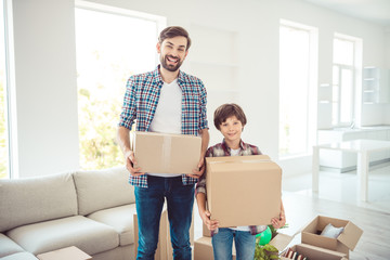 Young happy smiling family daddy and son two persons wearing casual holding carton boxes with stuff things in light studio living room, moving to new flat