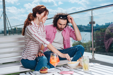 Bad quality. Curly man feeling extremely surprised looking at bad quality of fries sitting on terrace