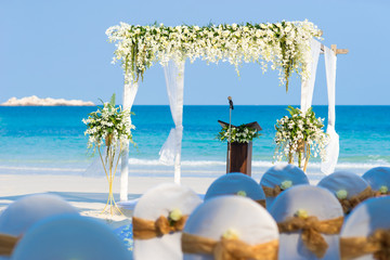 Close-up beautiful beach wedding arch setting with white flowers and green leafs decoration, panoramic ocean view