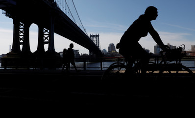 People are seen in silhouette underneath the Manhattan Bridge during sunny weather in Manhattan, New York