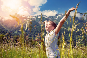 Cheerful child in tall grass against  backdrop of beautiful mountains Wall mural