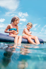 Happy smiling children, sister and brother, sit on inflatable raft