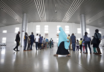 A woman walks past passengers queuing at the ticket checking point of the newly commissioned Abuja light rail train network in Abuja